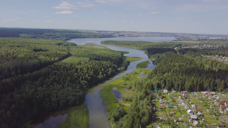 Aerial view of small town near forest. Clip. Aerial view of the town in a wooded area with river.