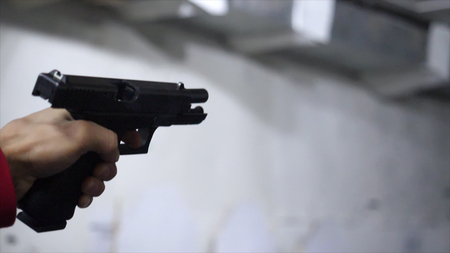 Gun in the mans hand. Man holding a gun close-up. Black handgun in hand of a man.