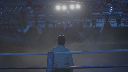 Back view of working gaffer or lighting technician and spotlights background. Lighting technician, placing the light during a film. Lighting technicians operating strobes during a concert