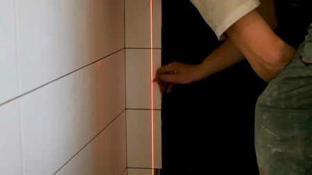 Man hands measuring with laser level gauge. Laser level gauge light. man with laser level check floor and walls