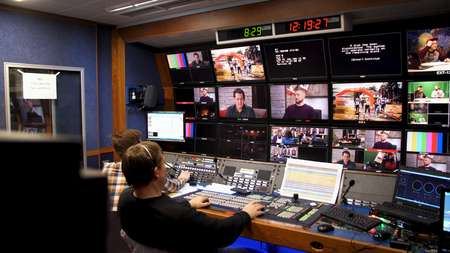Russia, Moscow - 12 January, 2017: TV director at editor in studio. TV director talking to vision mixer in a television broadcast gallery.Man sat at a vision mixing panel in a television studio gallery. Live TV broadcasting process. Sajtókép