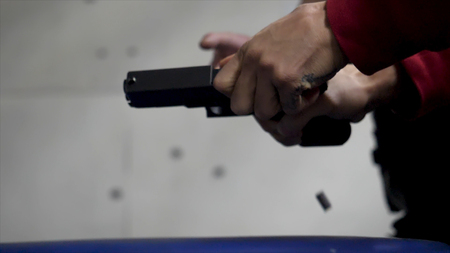 Trainer is teaching man to shoot a gun close up. Close up of male hands with a gun, man trains to shoot. Special police unit in training, school. Military shooting Short Gun Imagens