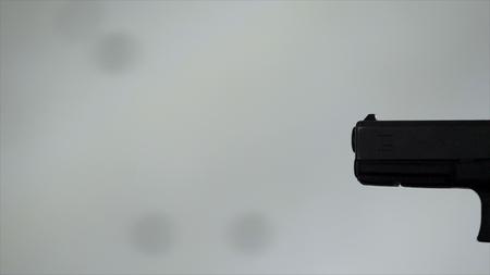 Close profile of man holding a 9 mm handgun, then takes a shot. Man fires hand gun at indoor shooting range. Close up. Man with 9 mm handgun takes a shot. Shot from above with an angle. Man holding a 9 mm handgun Standard-Bild - 96760853