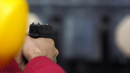 Back view of man shoots a gun at shooting range close up. Man fires hand gun at indoor shooting range. Close up. Close up of male hands with a gun, man trains to shoot rear view Imagens - 96760862