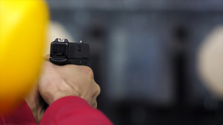 Back view of man shoots a gun at shooting range close up. Man fires hand gun at indoor shooting range. Close up. Close up of male hands with a gun, man trains to shoot rear view