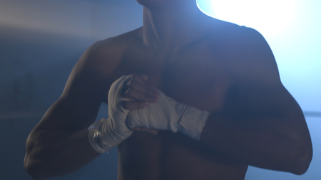 Half-length portrait of nude boxer with hands on hips, on dark background with light, close up. Young handsome male fighter standing concentrated before fight with putting palms together