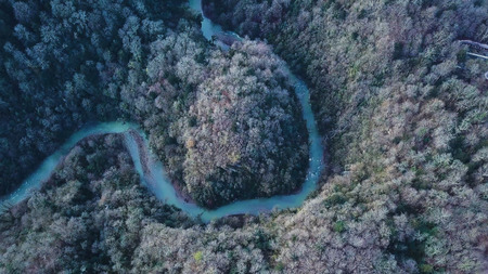 Top view on winding river and mountain. Clip. Aerial View on flying over the beautiful mountain River and beautiful forest. Aerial camera shot. Landscape panorama. flight over mountain river