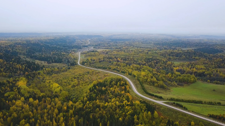 Aerial view of unlimited space of forest plain and cars which are riding on highway. Clip. Road in the autumn forest aerial view. aerial view over road between forests 版權商用圖片