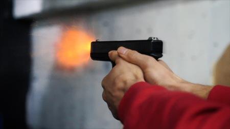 Gun is shot close-up. Pistol in hand close-up. Pistol being shot 1 times. Man shoots a black gun.