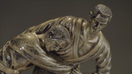 Bronze statuette of two men wrestling with each other close up. Champion wrestling Cup. Metal figurine on wrestling. Stock Photo