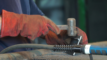Hand Ironworker forging hot iron in workshop whith hammer. Hands of blacksmith making horseshoe