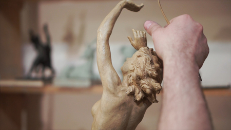 Sculptor corrects arm of female figurine by special tool. Clip. Sculptor Uses Tool To Sculpt Side Of Statue. Sculptor is working on the creation of a monument.