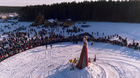 Moscow, Russia - February 26, 2018: Aerial view of Traditional burning of Maslenitsa Scarecrow. Burning of Scarecrow. Aslenitsa celebration. Man sets fire to a big doll-scarecrow on a stage in a city park