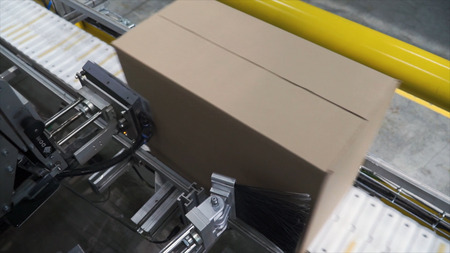 Cardboard boxes on conveyor belt in factory. Clip. Production line on which the boxes move. Banco de Imagens