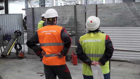 Rear view of workers talking while walking in shipping yard. Clip. Back view of two men in white safety hard hats are standing together in construction area Stok Fotoğraf