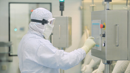 Worker At Pharmaceutical Factory. Lab technician working inside a pharmaceutical factory. Pharmaceutical manufacturing. Operating control panel of the pharmaceutical machine