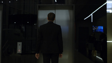 Man in business suit standing near the elevator, view from the back. Stock. businessman standing at elevator. Man in a business suit standing in the hallway near the elevator