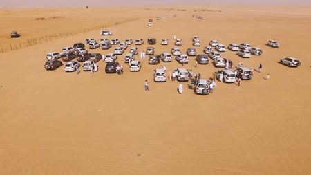 4x4 SUVs cars driving through the sand dunes in the desert of Abu Dhabi. Stock. Top view on SUVs in the desert Standard-Bild - 102257966