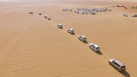 4x4 SUVs cars driving through the sand dunes in the desert of Abu Dhabi. Stock. Top view on SUVs in the desert
