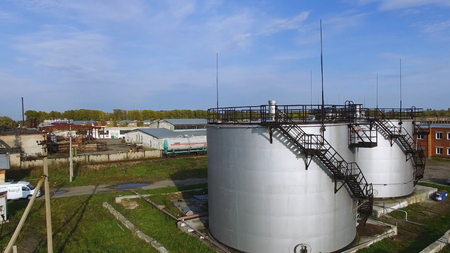 Aerial view white fuel storage tank in oil refinery plant. Stock. Top view white Industrial tanks for petrol and oil. Top view of the tank farm.