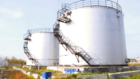 Large white Industrial tanks for petrol and oil. Stock. Fuel tanks at the tank farm. Big Industrial oil tanks in a refinery Stock Photo