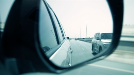 Close-up shot of a side rear view mirror of car. Stock. Side view mirror view of cars driving behind on a highway.