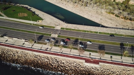 Aerial flying shot following cars on the highway alongside a rocky coast. Stock. Aerial view of Coastline along and highway.