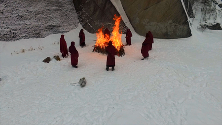 People stay around the campfire. Footage. People stay around the fire at night. group of monks near the fire in the mountains at dusk, top view.