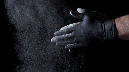 Cotton hands with flour on black background. Frame. Chef clapping hands covered in flour