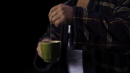 Man in a Bathrobe with a Cup of tea. Stock. A man makes tea on a black background. Bad mood concept Stockfoto