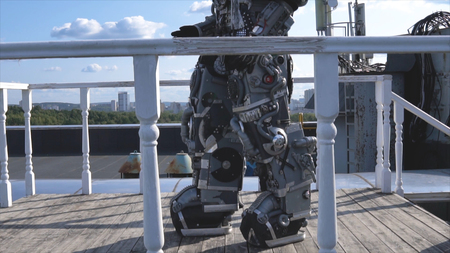 Robot moves his hands on background of city skyline and blue sky. Footage. Concept of technologies with artificial intelligence