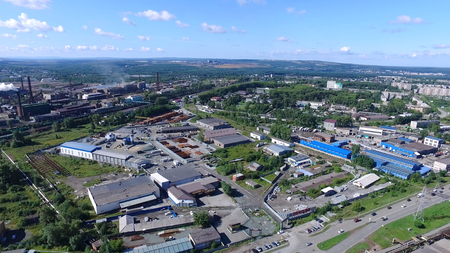 View from air on industrial zone in urban environment. Footage. Panorama from above offers view of industrial zone in city and stretches to horizon on clear day with blue sky. Industrial concept