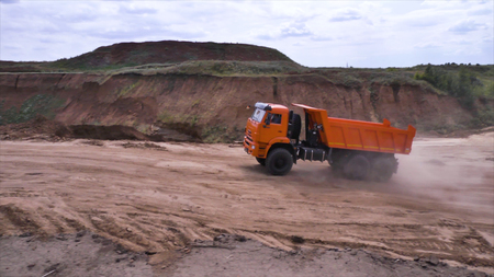 View of driving dump truck on sandy soil. Scene. Orange dump truck rides on quarry with ground in lowlands Stockfoto