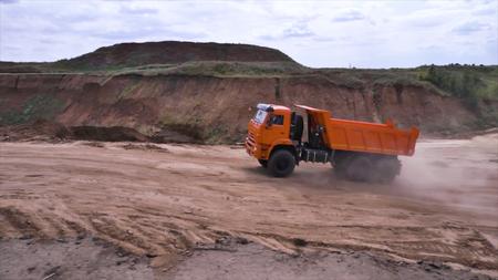 View of driving dump truck on sandy soil. Scene. Orange dump truck rides on quarry with ground in lowlands Reklamní fotografie
