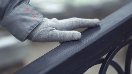 Close-up of young girls hand sliding over railing. Hand in grey glove touches railing outdoors in cold weather Imagens