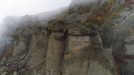 Slope of mountain in mist. Shot. Dense gray fog envelops entire space. Top view of rock plunging into cold autumn fog.