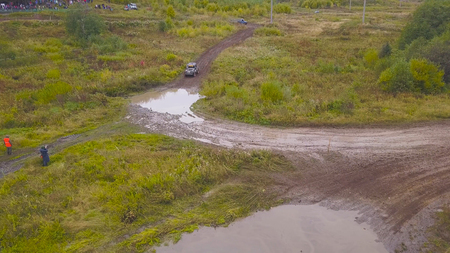 View of SUV driving into puddle. Clip. Top view of SUV driving into puddle of mud at races. Off-road racing in open forest area.