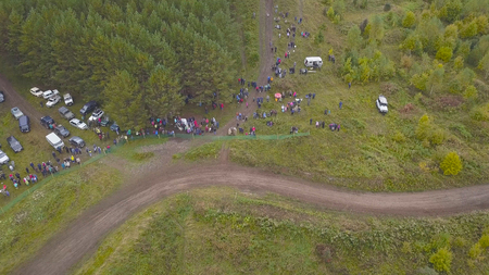 Top view of off-road racing with SUVs. Clip. View of finishing SUV racing in forest against crowds of fans. Standard-Bild - 113499851