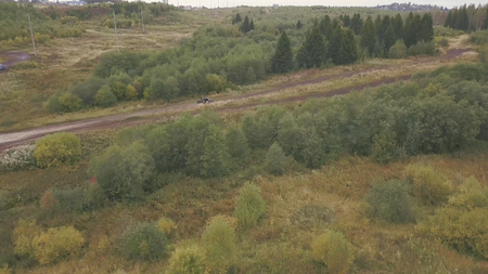 Extreme Motorsport of SUVs driving on country road. Clip. Top view of race track for SUVs in forest. SUV rides at speed on straight rural road in forest. Standard-Bild