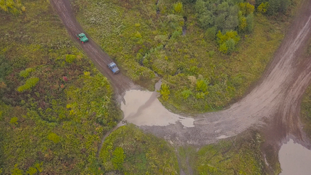 View of SUVs riding on puddle. Clip. Top view of surmounting puddles of SUVs on mud races. Jeep racing.