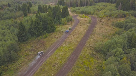 Top view of SUVs driving on country road. Clip. Off-road racing on mud roads in rural forest area.