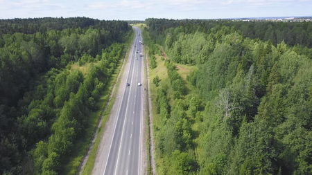 Top view of highway in forest. Clip. Traffic on rural road with city in background in cloudy sky.