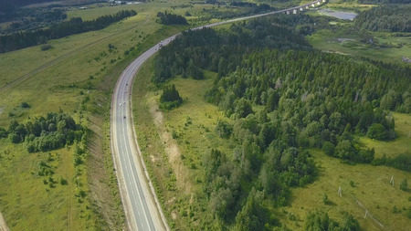 Countryside road surrounded by lush green nature. Clip. Top view of rural road in forest. Traffic on rural roads.