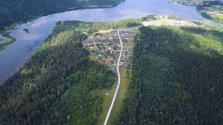 Aerial view of road among the forest and trees. Overhead aerial top view over straight road in colorful countryside autumn forest. Straight-down above perspective. Road through the green spruce forest, aerial view. Imagens