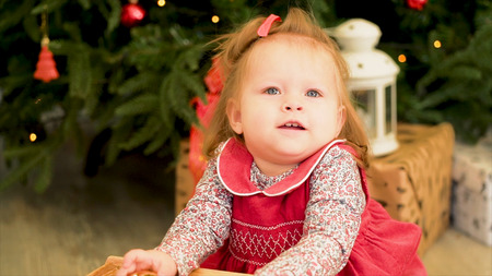 Christmas children. Cute little child near tree. Christmas kids. Little girl playing with toys near the Christmas tree