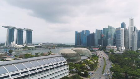 Singapore - 25 September 2018: Singapore city skyline along Singapore River, beautiful green grass and the road. Shot. Aerial for Singapore coastal skyline, high rise buildings and green park. 에디토리얼