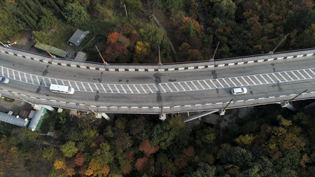 Top view on overpass with driving cars, sea and beautiful landscape background. Aerial view of highway and overpass in city. Road junctions. Imagens