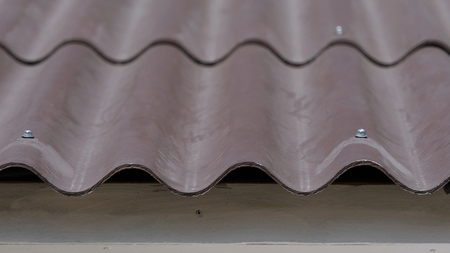 Close-up of roof tiles at home. Curved wavy roof tile of house is made practical and prudent. Practical roof design Stock Photo