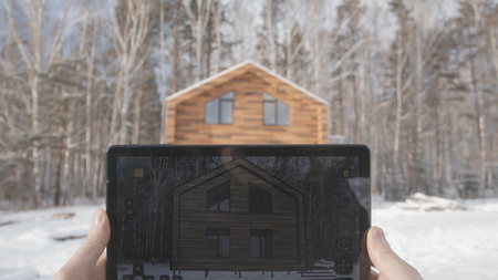 Man is making architecture photography with tablet in winter, home and building concept. Stock. Hands men take photos at home