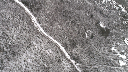 Top aerial view of snow mountain landscape with trees and road. Shot. Top view of the road in snowy forest